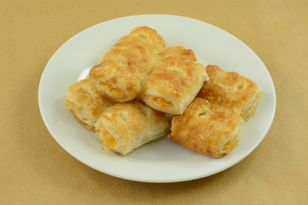 Stack of mini apple breakfast turnovers on white plate on table