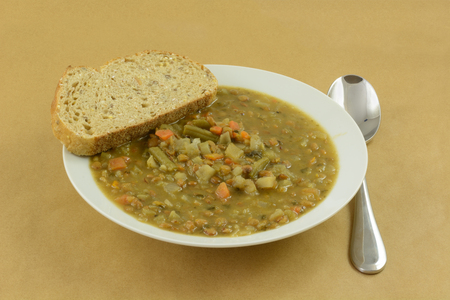 Lentil vegetable soup with slice of bread in white soup bowl with soup spoon Reklamní fotografie