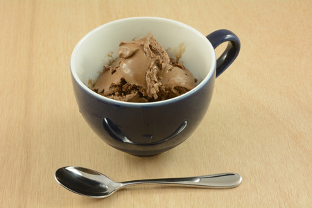 Chocolate ice cream in blue and white cup with spoon Reklamní fotografie