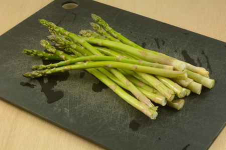 Bunch of freshly rinsed whole raw asparagus spears on black cutting board