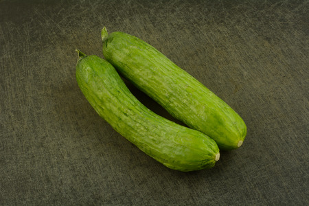 Two whole raw freshly rinsed Persian cucumbers on black cutting board