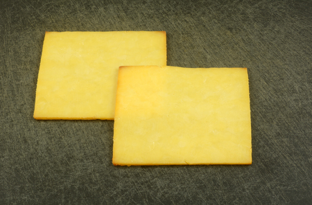 Two smoked gouda cheese slices on cutting board for food preparation Reklamní fotografie