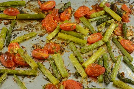 Roasted asparagus and tomato slices sprinkled with olive oil on aluminum foil on baking sheet Reklamní fotografie