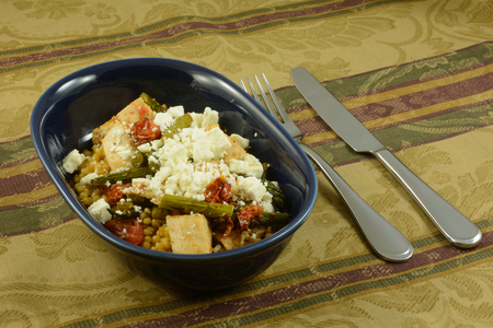 Israeli couscous or ptitim covered with chicken, roasted vegetables of asparagus and tomatoes with feta cheese on top in oval blue dish