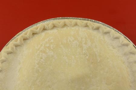 Close up of uncooked frozen apple pie on red background