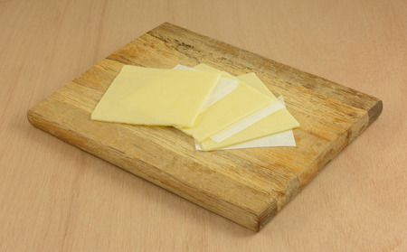 Close up of white cheddar cheese slices separated by paper on wooden cutting board in preparation for making food