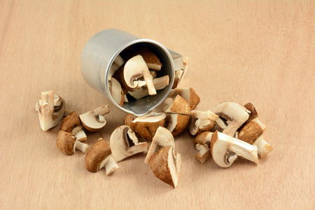 Quartered baby portabello mushrooms spilling out of retro vintage metal measuring cup onto wooden table Reklamní fotografie