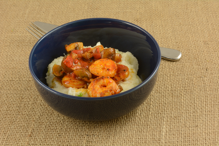 Shrimp and cheese grits with mushrooms and red peppers in blue bowl with fork on burlap