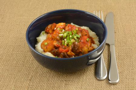 Shrimp and cheese grits with mushrooms and red peppers in blue bowl with knife and fork on burlap Reklamní fotografie