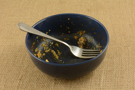 Empty blue bowl with fork with last remnants of cheese grits at end of meal