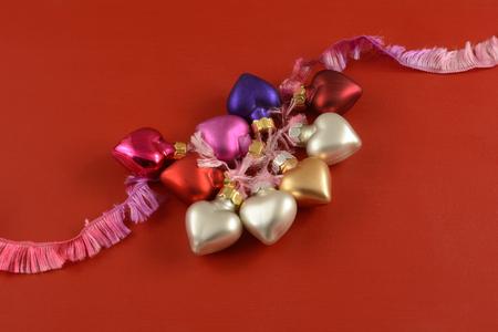Valentines Day heart ornaments on pink ribbon on red wooden background Reklamní fotografie
