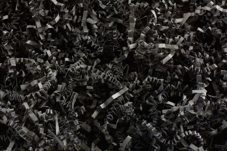 Close up of crinkled shredded black paper box filler for shipping fragile items to prevent damage and breakage