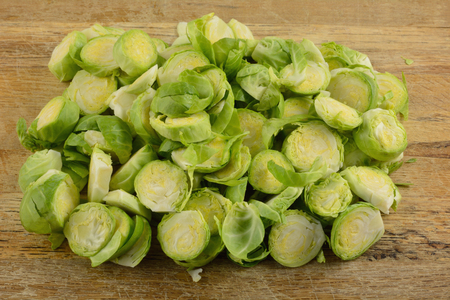 Close up of sliced fresh raw brussel sprouts on rustic cutting board