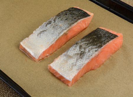 Two cuts of fresh raw salmon fillets on parchment paper on baking sheet with skin and scale side up Reklamní fotografie
