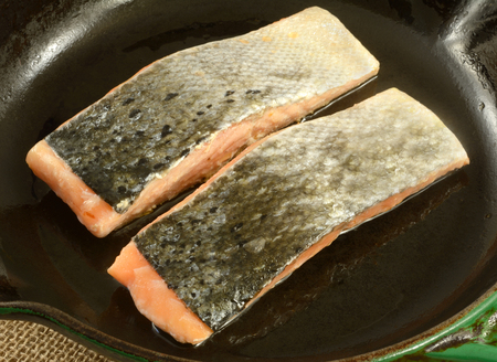 Close up of two raw salmon fish fillets skin side up in cast iron frying pan coated in olive oil Reklamní fotografie