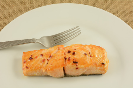 Baked salmon fish fillet with crushed red pepper glaze on white late with fork Reklamní fotografie