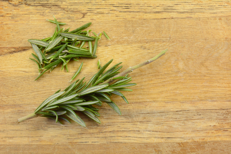 Fresh herb rosemary leaves and partially stripped twig of rosemary on wooden cutting board Reklamní fotografie