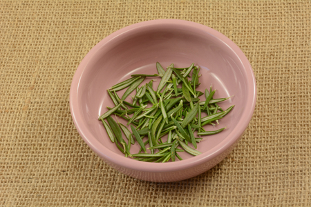 fresh green rosemary herb leaves in small pink condiment bowl on burlap Reklamní fotografie