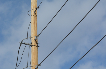Electric power lines attached to new wooden pole against cloudy blue sky Reklamní fotografie