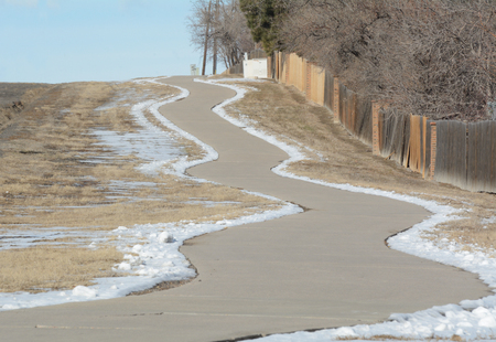 Clean sidewalk with snow on edges climbing up hill with fence and winter bare trees on one side