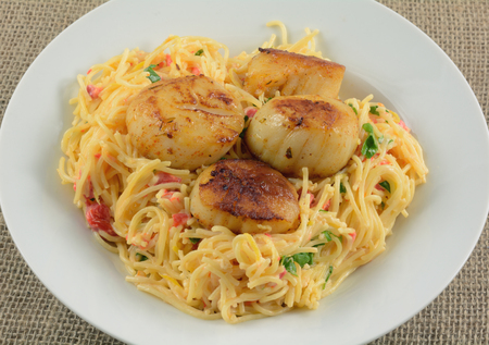 Grilled spicy sea scallops on cheesy pasta in white bowl