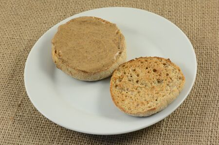 Almond butter on toasted English muffin on small white breakfast plate