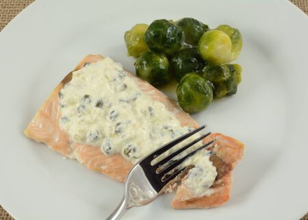 Baked salmon fillet with light cream sauce with capers and brussel sprouts in a light butter sauce on white plate with fork