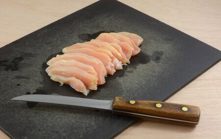Raw chicken boneless breast meat slices on black cutting board with knife