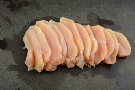 Raw sliced chicken boneless breast meat on black cutting board Foto de archivo - 131144733