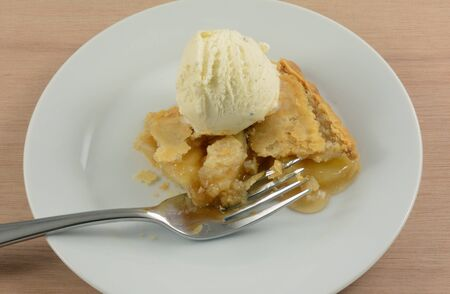 Slice of apple pie with scoop of French vanilla ice cream on white dessert plate with fork
