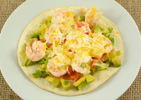Shrimp tostado with chopped avocado and tomato and melted cheese on white plate Foto de archivo