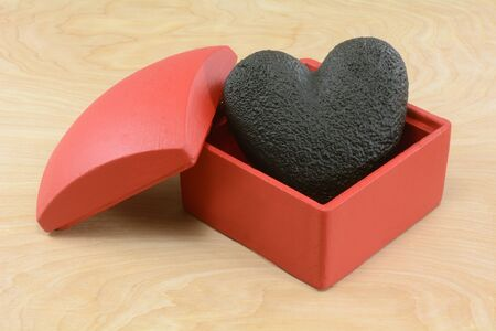 Anti-Valentines Day burned black charcoal heart in red box