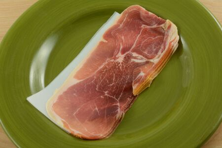 Thin uncooked prosciutto slices separated by butcher paper on plate to add as ingredient to meal 写真素材