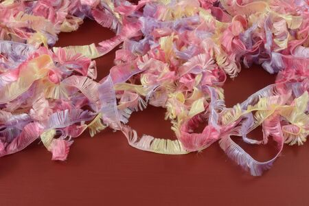 Background of strands of pastel colored yellow red and purple yarn or ribbon on red wood