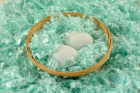 Two white eggs in wooden wicker basket surrounded by green fluffy yarn 写真素材