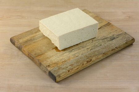 Block of extra firm tofu on cutting board to prepare for adding as ingredient to meal in cooking 写真素材