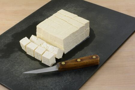 Block of extra firm tofu cut into cubes on cutting board with kitchen knife to prepare for adding as ingredient to meal in cooking 写真素材