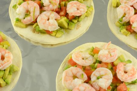 Shrimp tostados with chopped avocado and tomatoes on aluminum foil lined baking sheet 写真素材