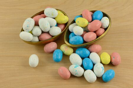 Candy covered malted milk chocolate for Easter in shape of bird eggs spilling out of brass Easter egg halves on wooden table 写真素材