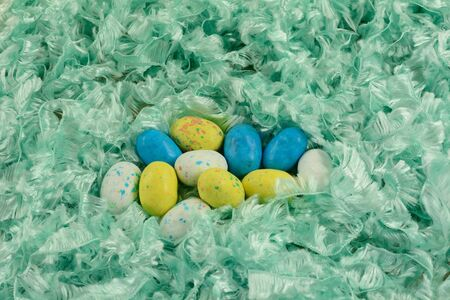 Candy covered malted milk for Easter in shape of bird eggs in nest of soft fluffy green ribbon