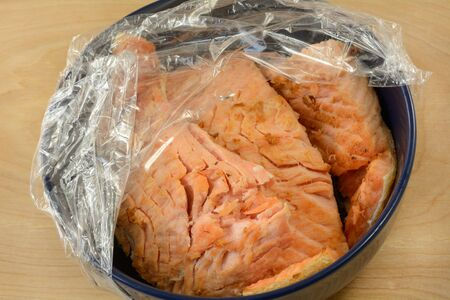 Left over baked salmon fish fillet meat in blue bowl with plastic wrap 写真素材
