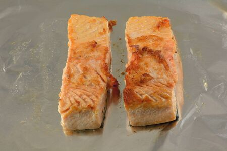 Two salmon fish fillets slices baked with olive oil on aluminum foil