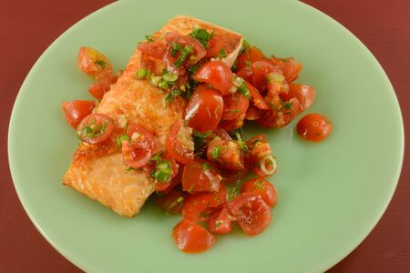 Baked salmon fish fillet with sliced grape tomatoes on green plate on red table