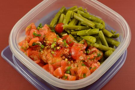 Baked salmon fish fillet with grape tomatoes and asparagus leftovers packed in plastic container for healthy work lunch