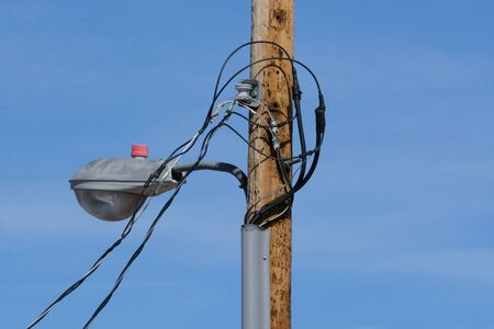 New urban streetlight on new wooden pole with new temporary power line cables attached but not yet completely installed