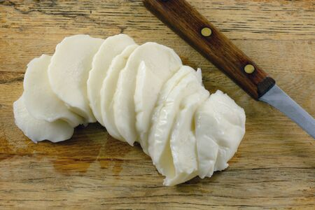 Fresh mozzarella cheese slices on wooden cutting board with kitchen knife 写真素材