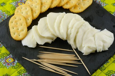 Snack of fresh mozzarella cheese slices and crackers with toothpicks on slate