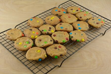Batch of candy covered chocolate piece cookies fresh out of the oven on cooling rack