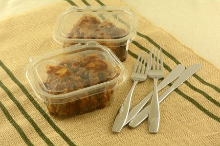 Two take out deli boneless chicken lunches in plastic containers with knives and forks on place mat Archivio Fotografico - 140951649