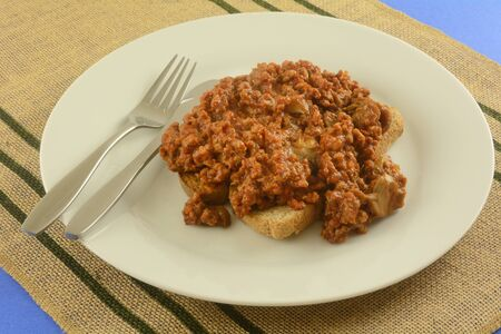 Sloppy Joe mix with canned mushrooms with toast on whte plate with fork and knife Archivio Fotografico - 143026017